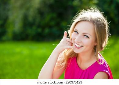 Beautiful woman making a call me gesture