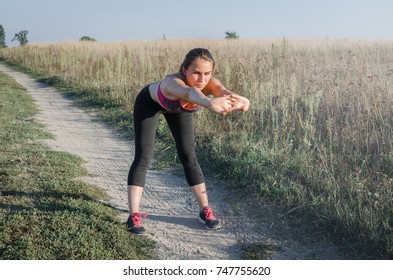 Beautiful woman making exercises on field road during sunset