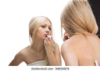 beautiful Woman making up her lips at bathroom