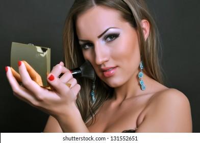 Beautiful woman making her makeup
