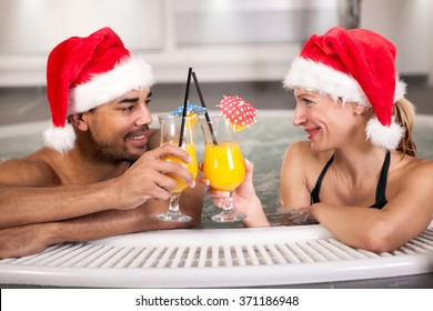 Beautiful woman and man with santa hat relaxing in jacuzzi at spa center