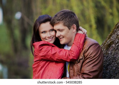 Beautiful woman and man are smiling on the background of green trees