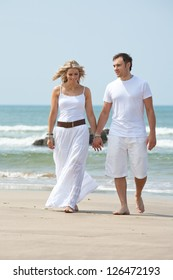 Beautiful woman and man walking on beach
