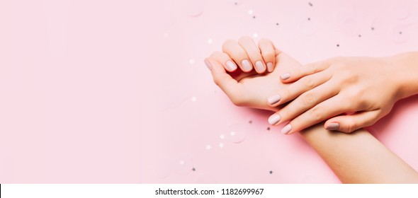 Beautiful woman manicure on creative trendy pink background with confetti. Minimalist manicure trend. Top view, flat lay. Copy space for your text.