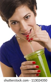 Beautiful woman with manicured nails sips a green smoothie
