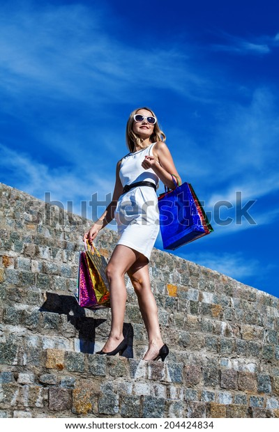 Beautiful woman with many shopping bags in city. Shopping and tourism concept