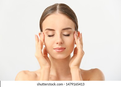 Beautiful woman massaging her face against white background
