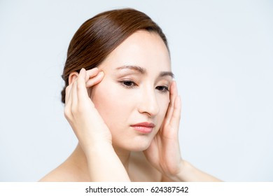 beautiful woman massaging her face. lymphatic massage.