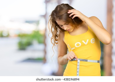 Beautiful woman measuring her waist with a measuring tape