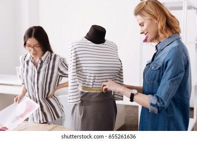 Beautiful woman measuring waist of a dress