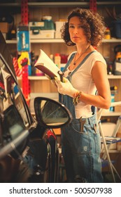 beautiful woman mechanic in blue overalls with instructions for repair and wrenches in a workshop for car repairs. professional auto repair in garage. instagram image filter retro style