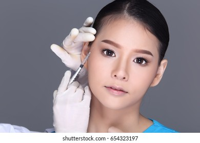 Beautiful Woman with Medical beauty Injection Treatment syringe over face before plastic surgery by doctor, Studio lighting white background isolated
