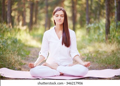 Beautiful woman meditating in nature