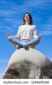 beautiful woman meditating on the rocks