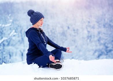 Beautiful woman meditating in winter park