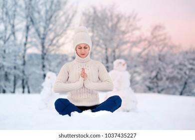 Beautiful woman meditating in yoga pose in winter park