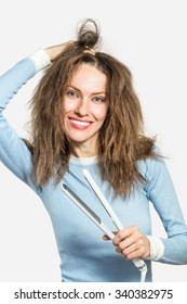 Beautiful woman with messy hair  holding straightening irons over grey background. Hairstyling. Hairdressing. Hair straightening irons