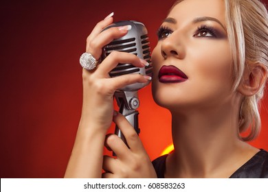 Beautiful woman with microphone. Close-up, studio, red background.