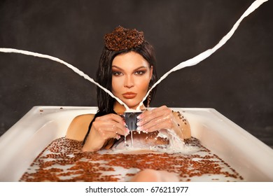 beautiful woman in the milk bath with coffee beans drinking a cup of espresso
