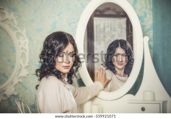 Beautiful woman in the mirror reflected the smiles magically in retro interior