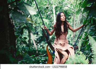Beautiful woman mixed race wearing gypsy natural cotton pink dress  seating on swing in jungle forest