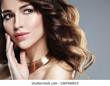 Beautiful woman model with curly hairstyle wearing elegant jewelry