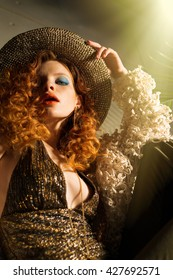 Beautiful woman model in the hat with red hair poses for the camera. Furnishings, clothing and design in the style of the 70s.