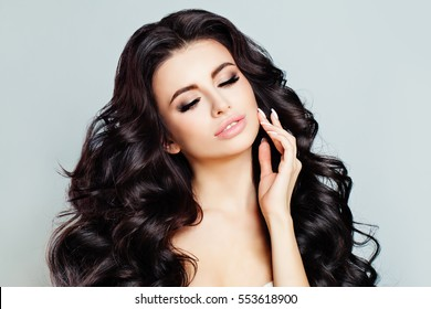 Beautiful Woman Model with Long Shiny Wavy Hair and Perfect Skin. Pretty Model with Curly Hairstyle. Skin Care Concept