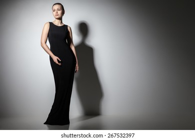 beautiful woman model posing in elegant black dress in the studio