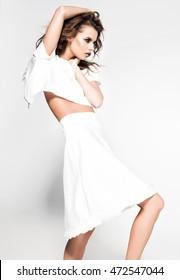 beautiful woman model posing in white dress in the studio