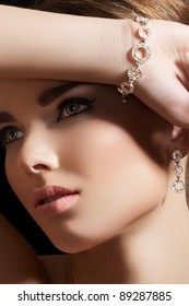 Beautiful woman model in retro style make-up. Accessories, jewelry gold bracelet and earrings with diamonds. Chic makeup and luxury jewellery