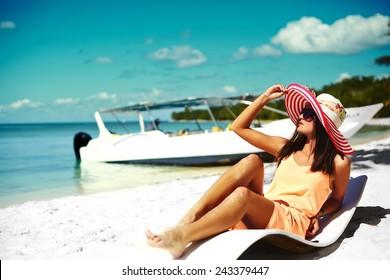 Beautiful woman model sunbathing on the beach chair in white bikini in colorful sunhat behind blue summer water ocean