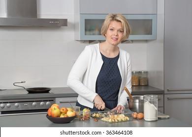 Beautiful woman in a modern kitchen, baking an apple pie