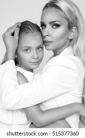 Beautiful woman mother with daughter snuggling together and show love, smartly dressed in a white dress on a white background