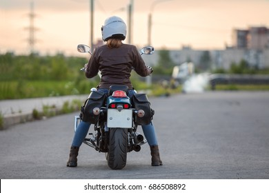 Beautiful woman a motorcycle driver waiting on the road at the evening, rear view