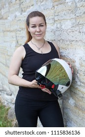 Beautiful woman motorcyclist posing with white open face helmet near stone wall