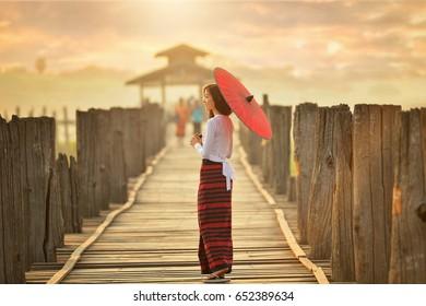 The beautiful woman Myanmar in U-ben bridge on during sunrise , treaditional culture ,Mandalay Myanmar