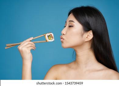 Beautiful woman naked shoulders sushi japanese chopsticks