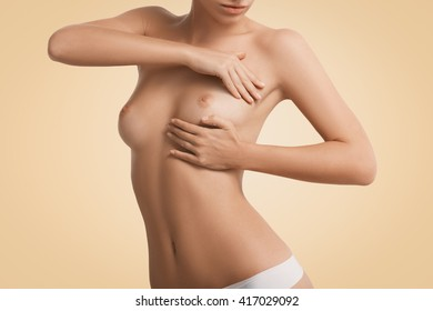 Beautiful woman with naked torso examining breast mastopathy or cancer pressing on her nude breast. Cropped shot of young  female with perfect tanned skin, flat belly and slim waist. Health concept