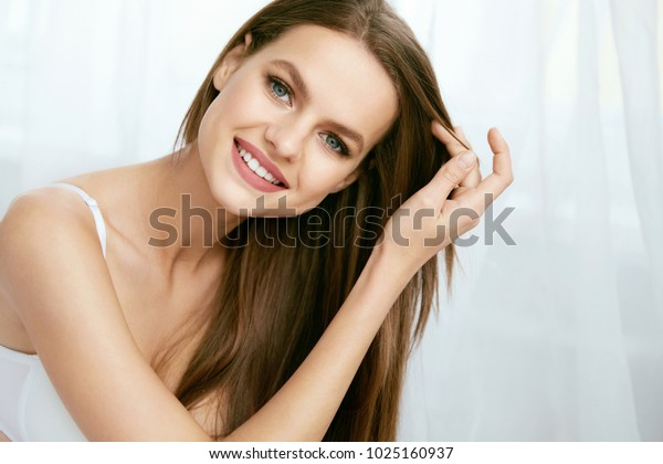 Beautiful Woman With Natural Makeup And Beauty Face. Portrait Of Happy Young Female With Fresh Makeup, Healthy Brunette Hair In Light Interior. Beauty Concept. High Quality Image.