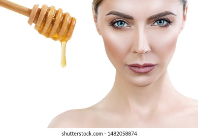 Beautiful woman near honey spoon with flows down honey prepare for honey facial mask.