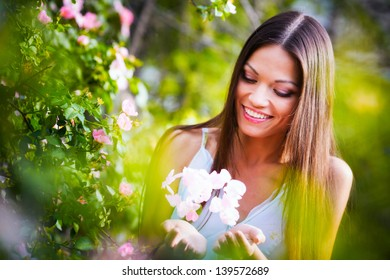 Beautiful woman near rose flower plant