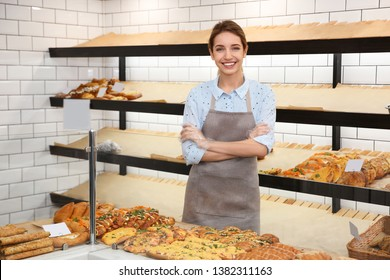 Beautiful woman near showcase with pastries in bakery shop