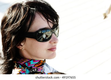 Beautiful woman in neckerchief and sunglasses relaxing under the sun