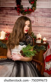 Beautiful woman in new year's style with a gift in hands on background of Christmas tree