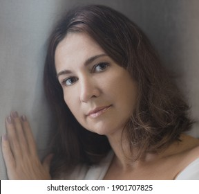 Beautiful woman next to the window. Lockdown concept. Shallow depth of focus