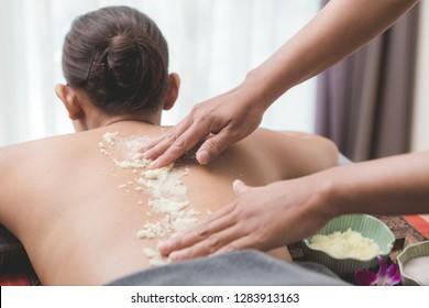 Beautiful woman njoying a salt scrub massage and having exfoliation treatment in spa room. Brunette getting a salt scrub beauty treatment in the health spa. Body Scrub.