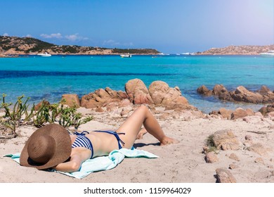 Beautiful woman on the beach enjoying the sun and the cool breeze of the ocean