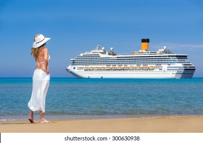 Beautiful woman on the beach watching a cruise ship passing by