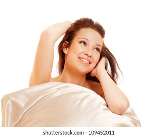 Beautiful woman on a bed and pillow isolated on white background